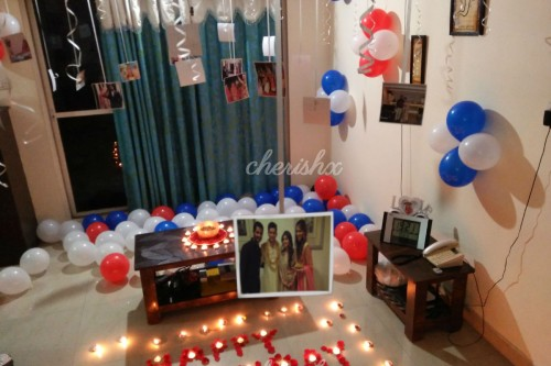 Room decoration with colourful balloons spread out on the floor and photos hanging from the ceiling available in Bangalore.