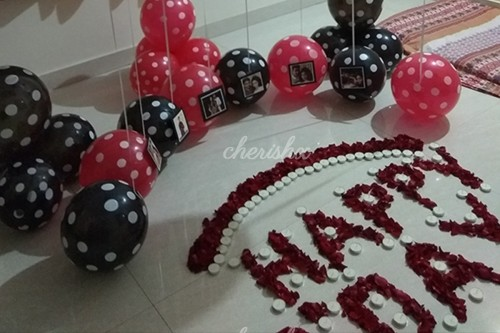 A decorated room with balloons, photos and candles for a midnight Birthday surprise.