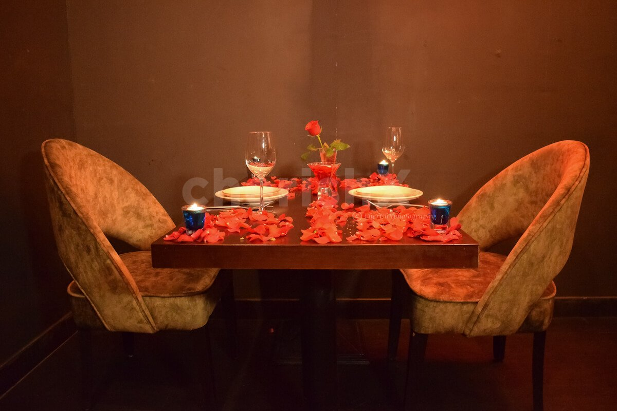 Have a romantic lunch on a well-decorated table with flower petals and candles.