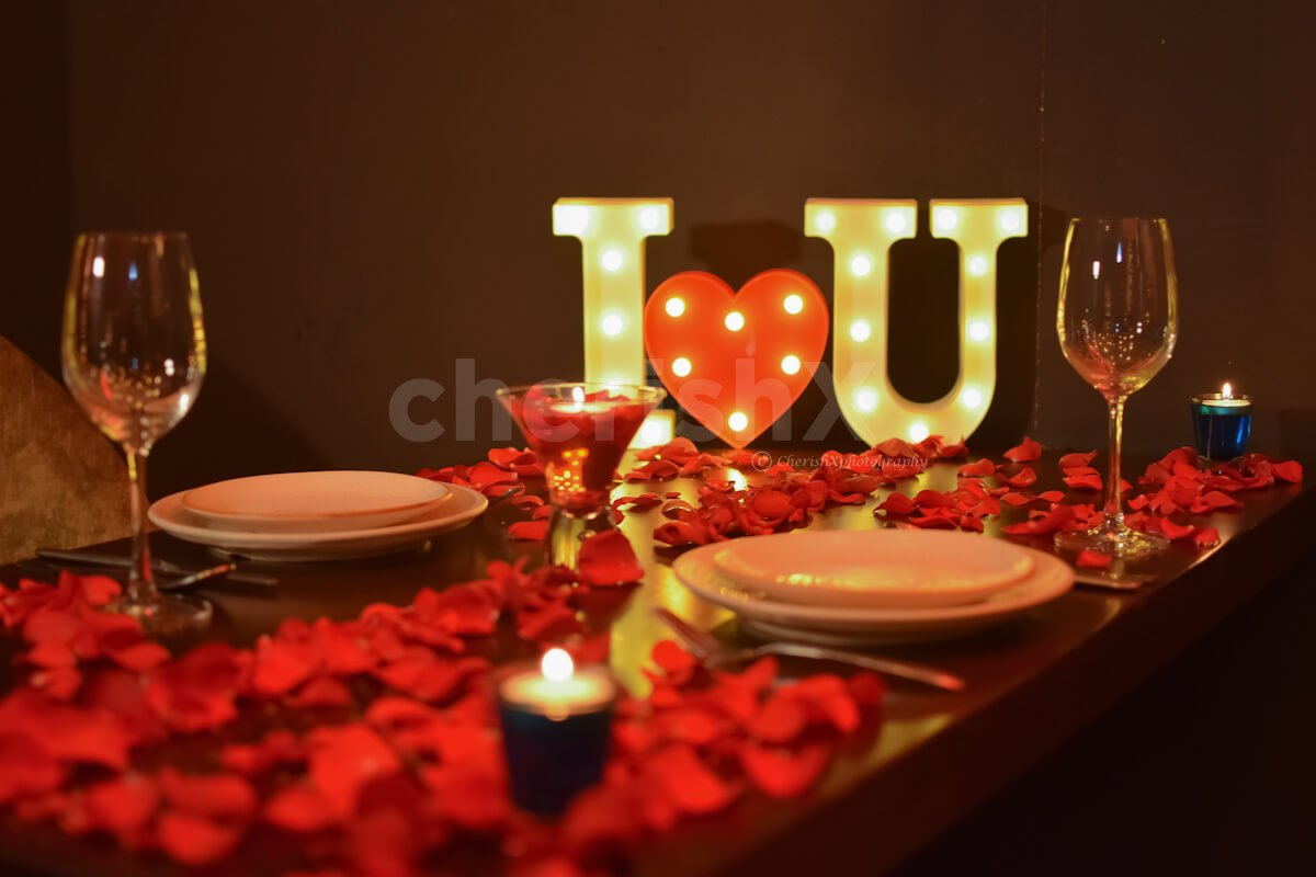 The table is beautifully decorated with rose petals and candles to give you romantic feels.