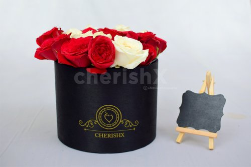 A bucket, full of red roses in which the letter is highlighted with white roses.