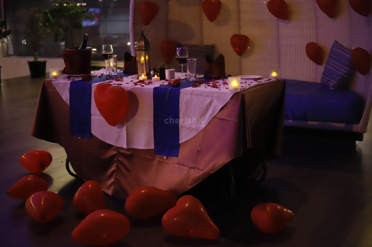 The Poolside Candle Light dinner experience is curated with balloons and rose petal decor.