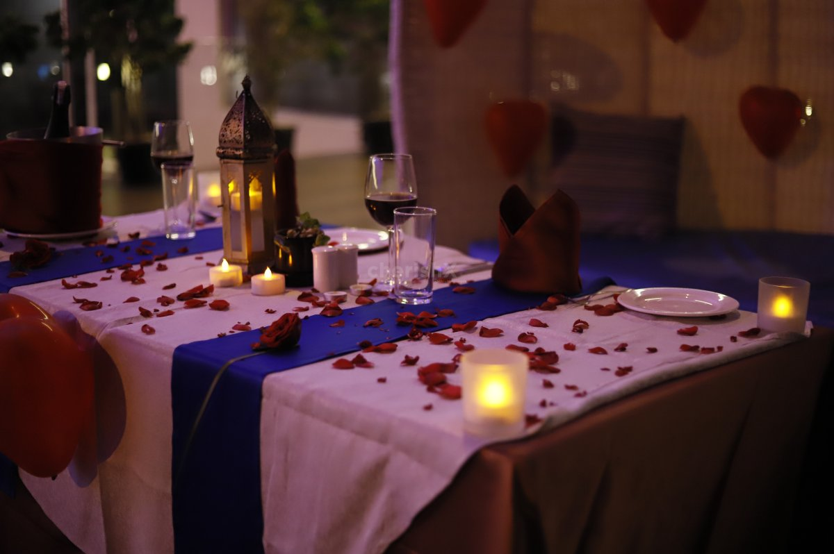 The poolside Romantic Candle Light Dinner table is decorated beautifully with candles and rose petals.
