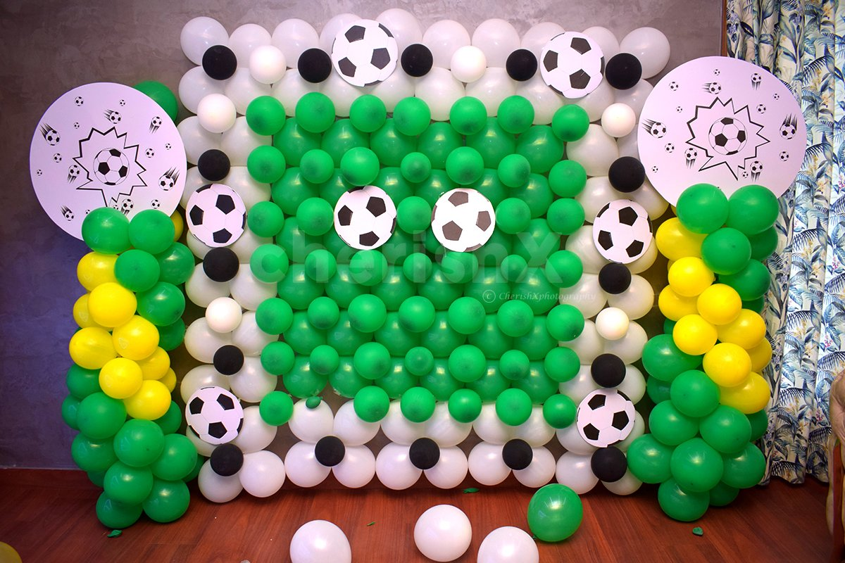 The wall is decorated with bunches of green, white and yellow balloons.