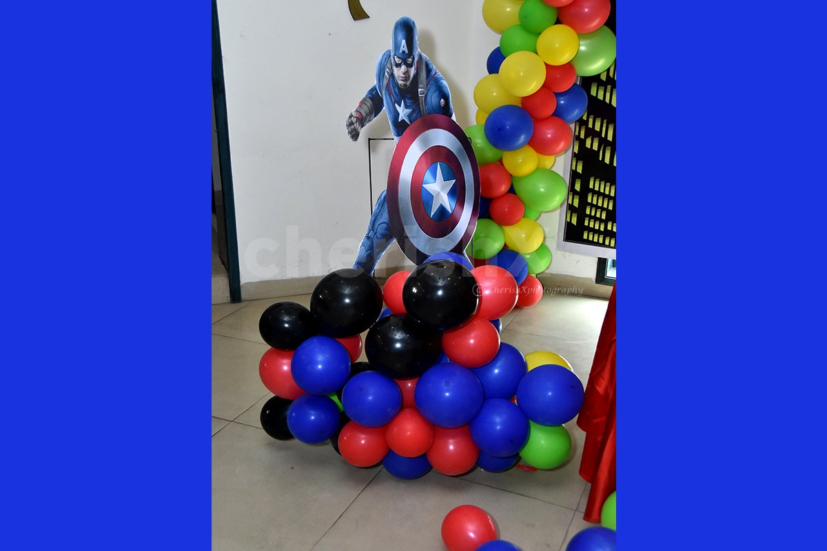 A Captain America Cut-out on a balloon bunch stand.