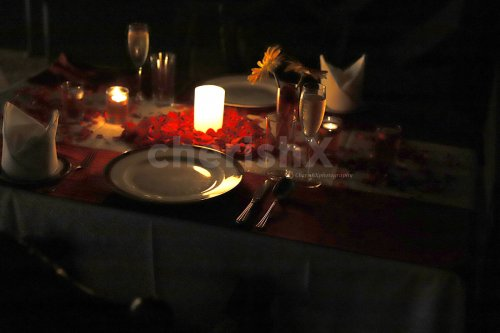 A Romantic Candle Light Dinner Arrangement with rose petals and candles.