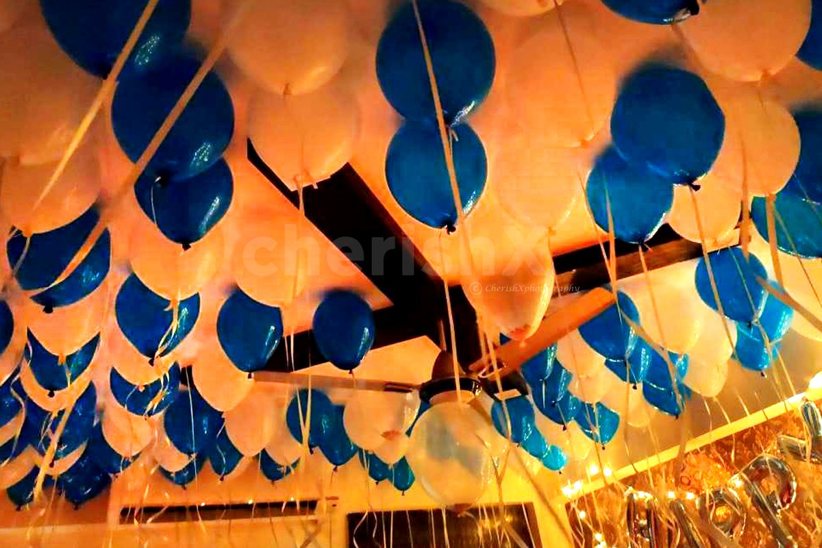 Blue and white balloons attached to the ceiling in preparation for a Balloon Surprise.