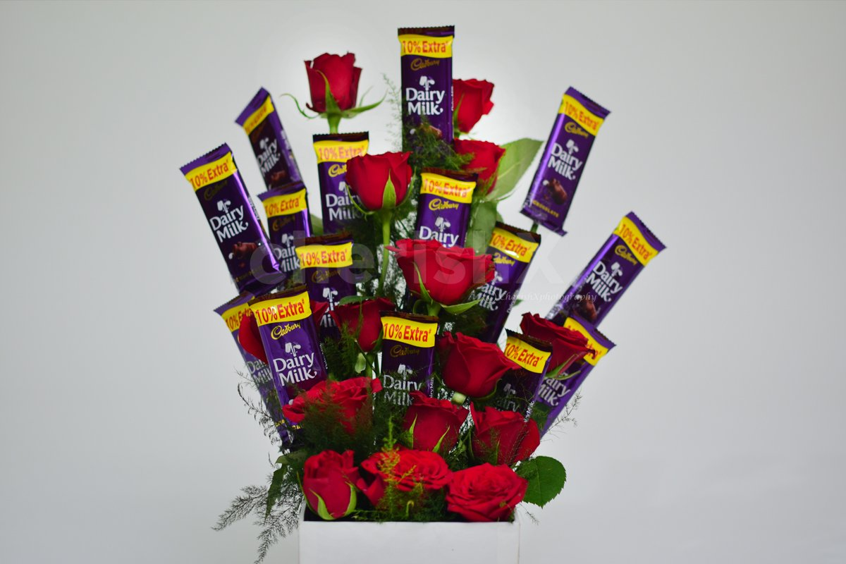 The chocolate and roses are arranged as a flower bouquet.