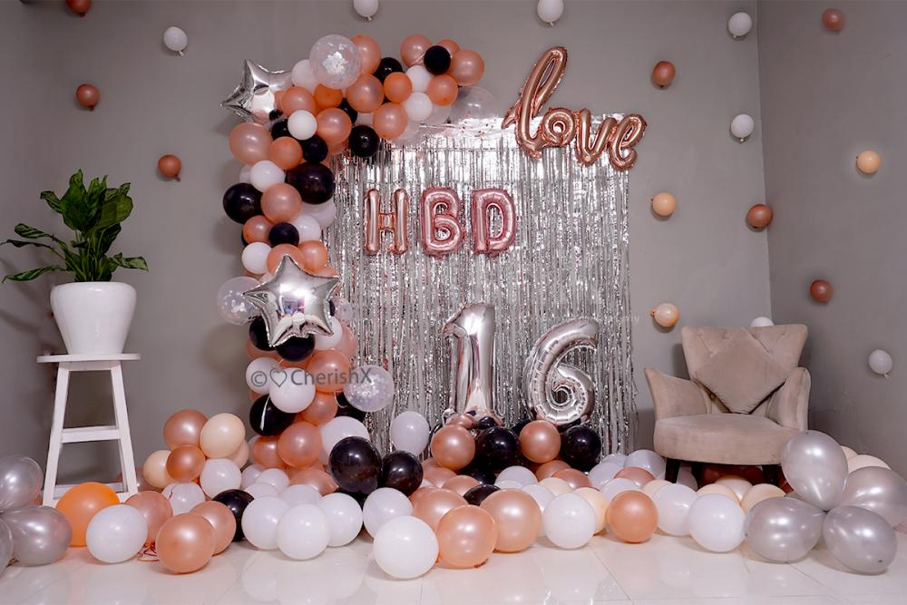Arc made of Rosegold, Black & White Balloons for a birthday room decoration.