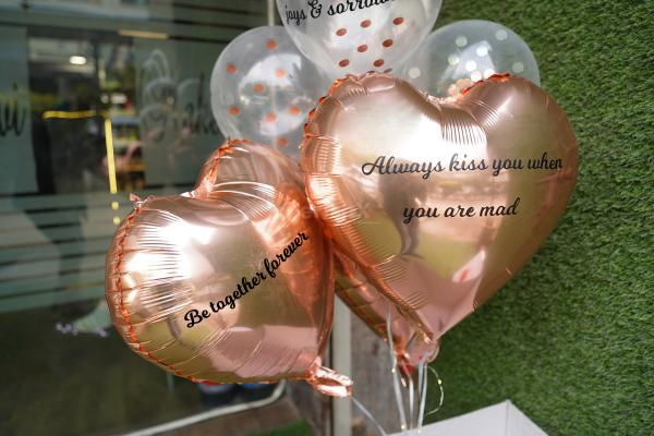 Two heart-shaped rose gold foil balloons with 1 promise on each.