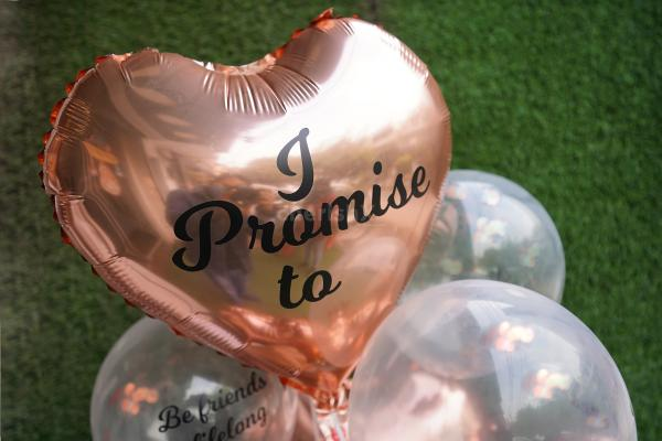 """A heart-shaped Rose Gold Balloon saying """"I Promise to"""" indicating to the 7 promises printed on other balloons."""
