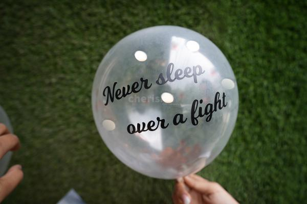 A helium confetti balloon with a 'never sleep over a fight' vinyl message.