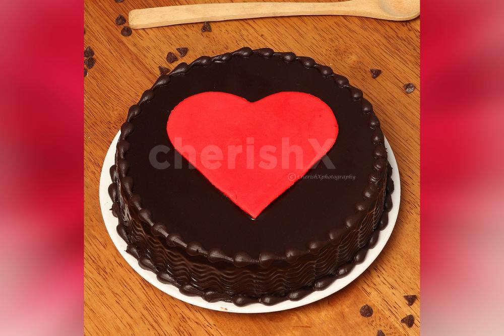 A chocolate flavoured cake with a heart on the top.
