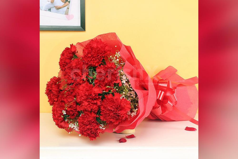A bouquet of 10 red carnations wrapped in red paper.