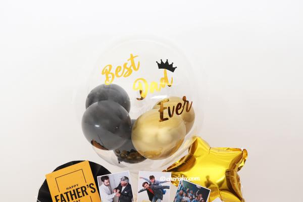 CherishX's Black & Gold Father's Day Bucket consists of a Bubble Balloon Filled with black and gold chrome balloons!