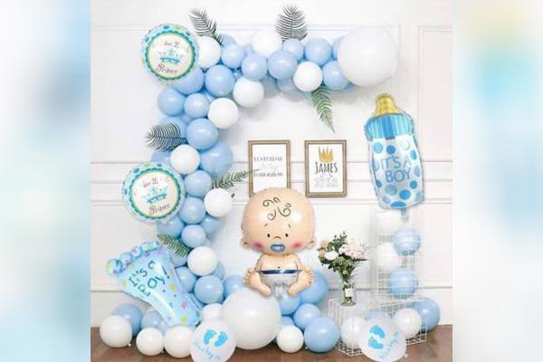 The balloon arch made up of pastel blue and white balloons with a Baby Face & Bottle Foil Balloons