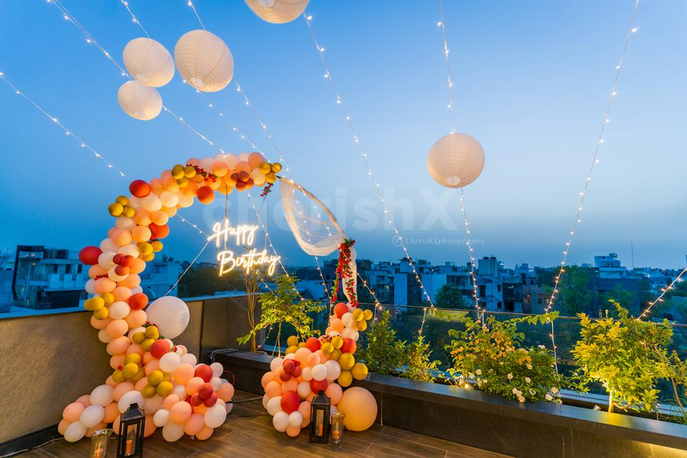 A terrace beautifully decorated with neon lights birthday decor .