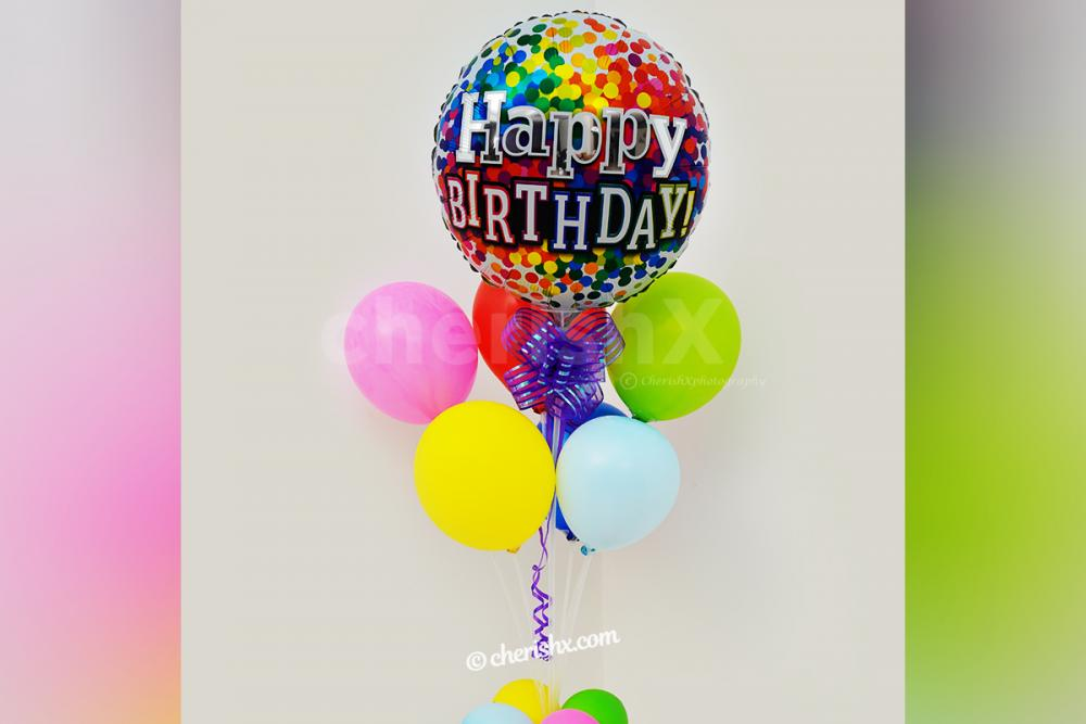 A birthday balloon Bunch stand with a purple ribbon for your party decorations