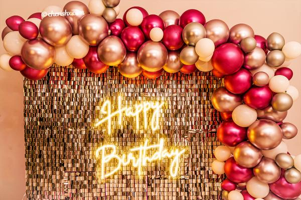A wall covered with an arc of silver and pink chrome balloons.