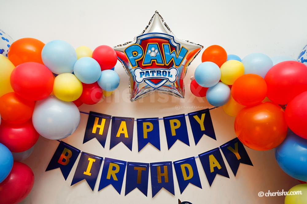 Silver star shaped foil balloon with PAW Patrol Badge Sticker on it.